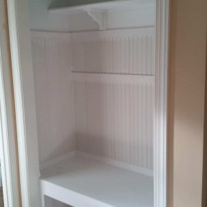 More than crown molding, this closet was custom fitted with a bench and wanescote