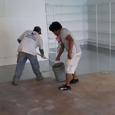 two guys applying epoxy paint on garage for Klappenberger & Son
