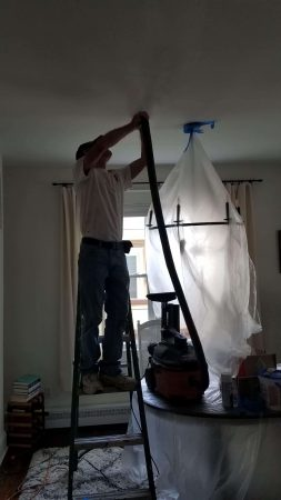 Interior painting contractor sand ceiling with a vacuum attachment